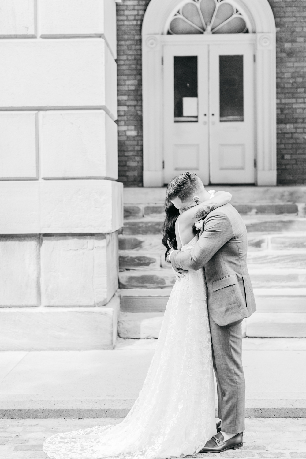 Bride and groom embracing after first look at Osgoode Hall in Toronto