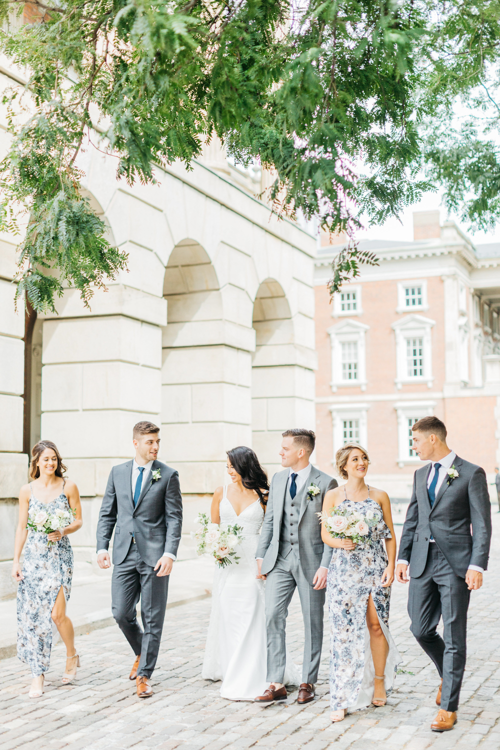Bride and groom with bridal party walking at Osgoode hall