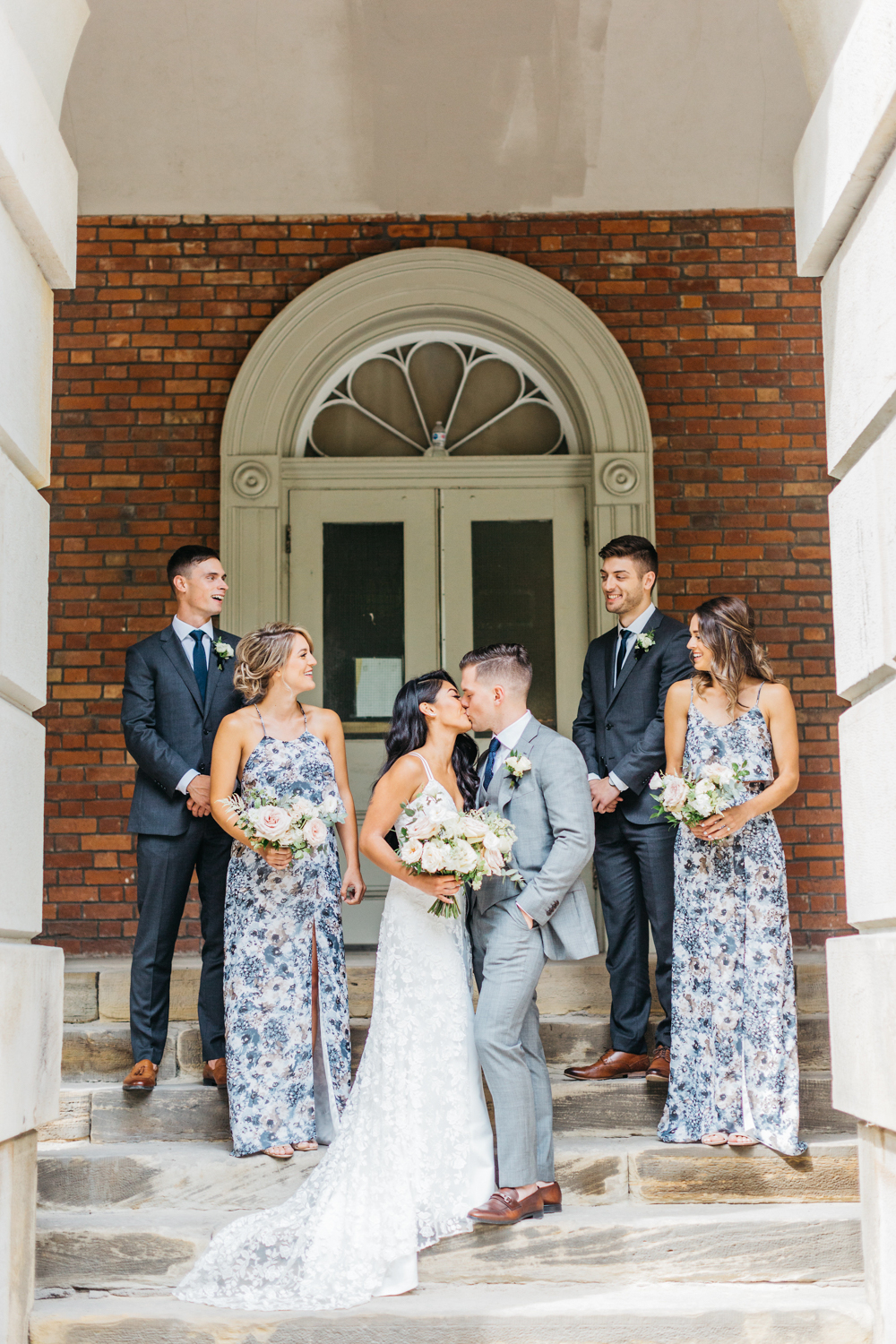 Bride and groom kissing while bridal party watches at Osgoode Hall