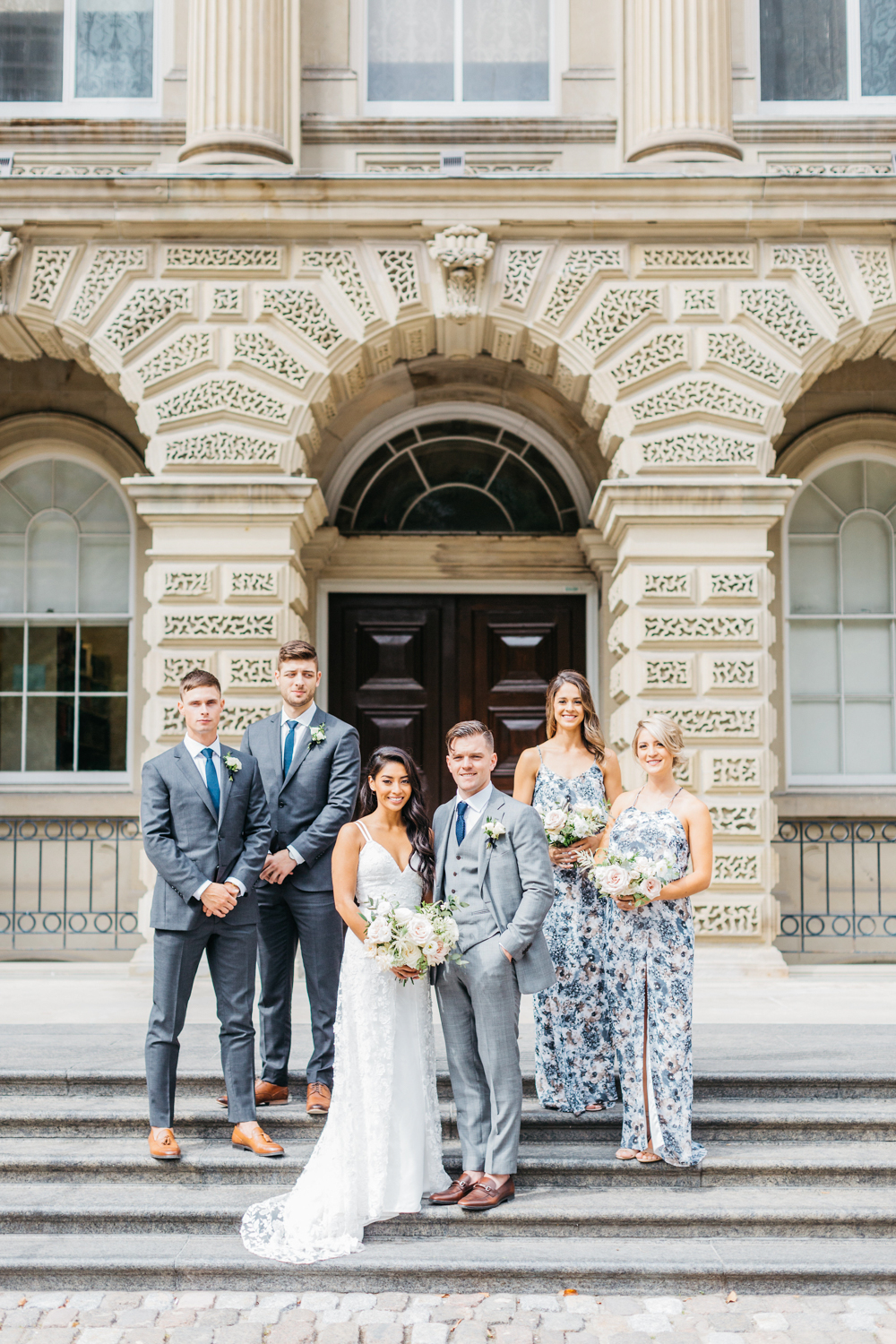 Bride and groom posing with bridal party as Osgoode hall