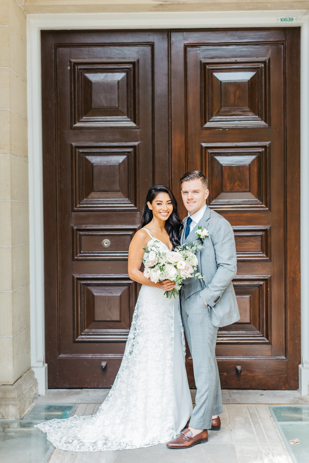 Bride and groom posing in front of doors at Osgoode Hall