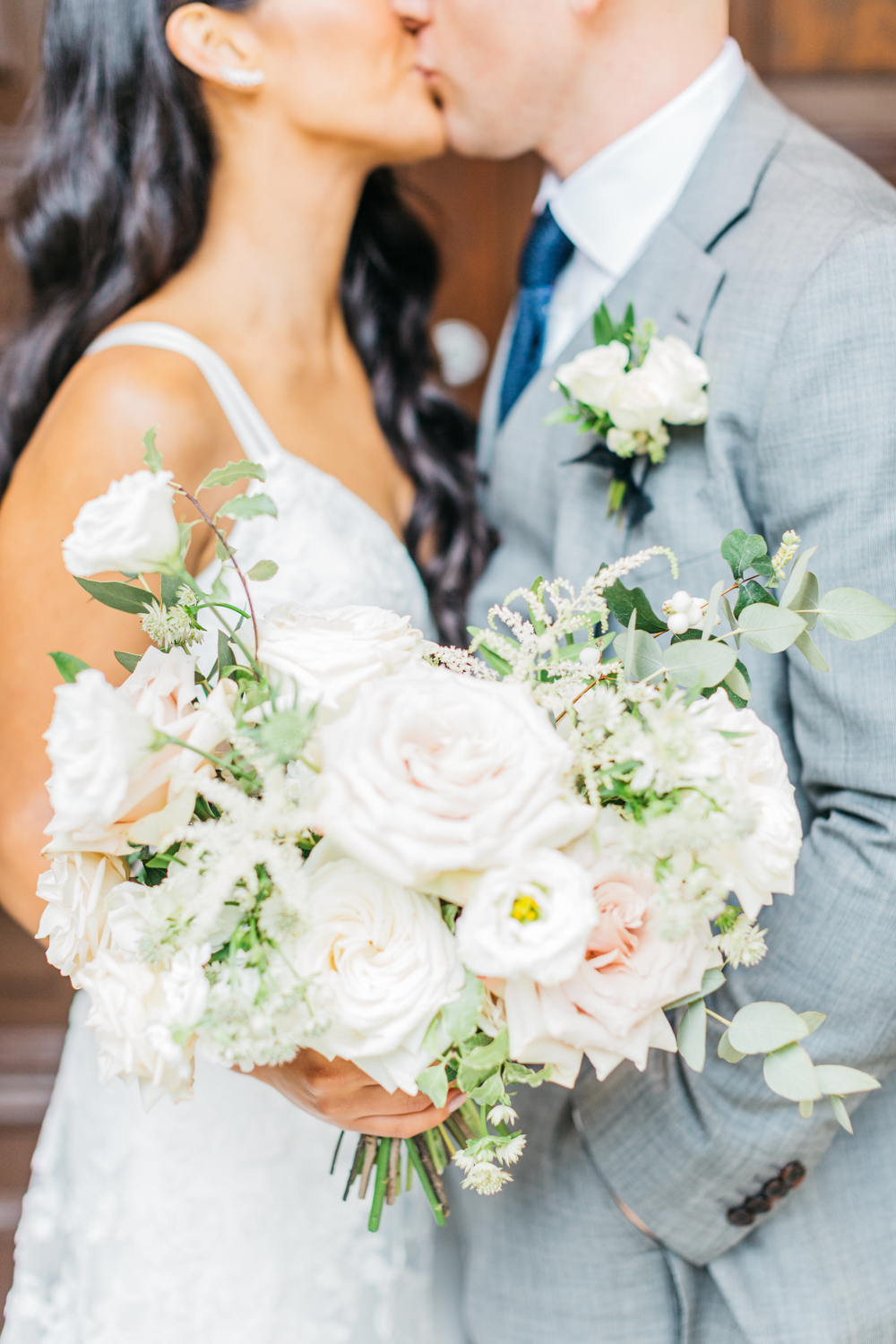 Bride and groom kissing with florals in front at Osgoode Hall