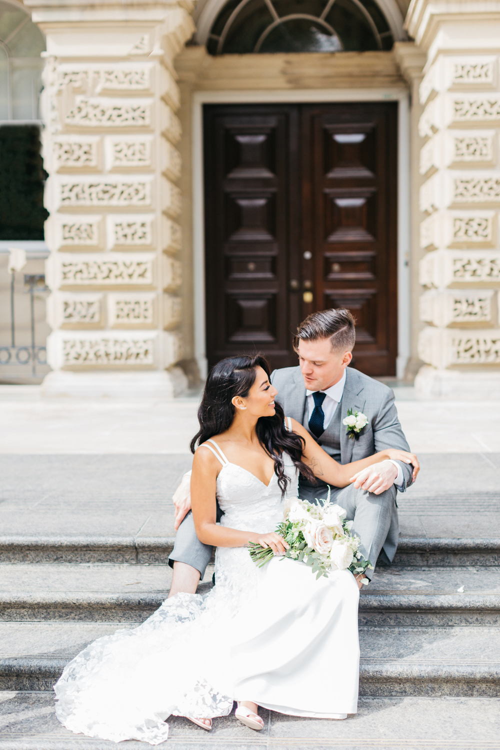 Bride and groom sitting on steps at Osgoode Hall