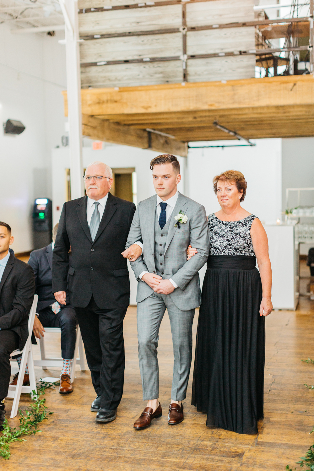 Groom walking down with parents during Ceremony at The Glass Factory