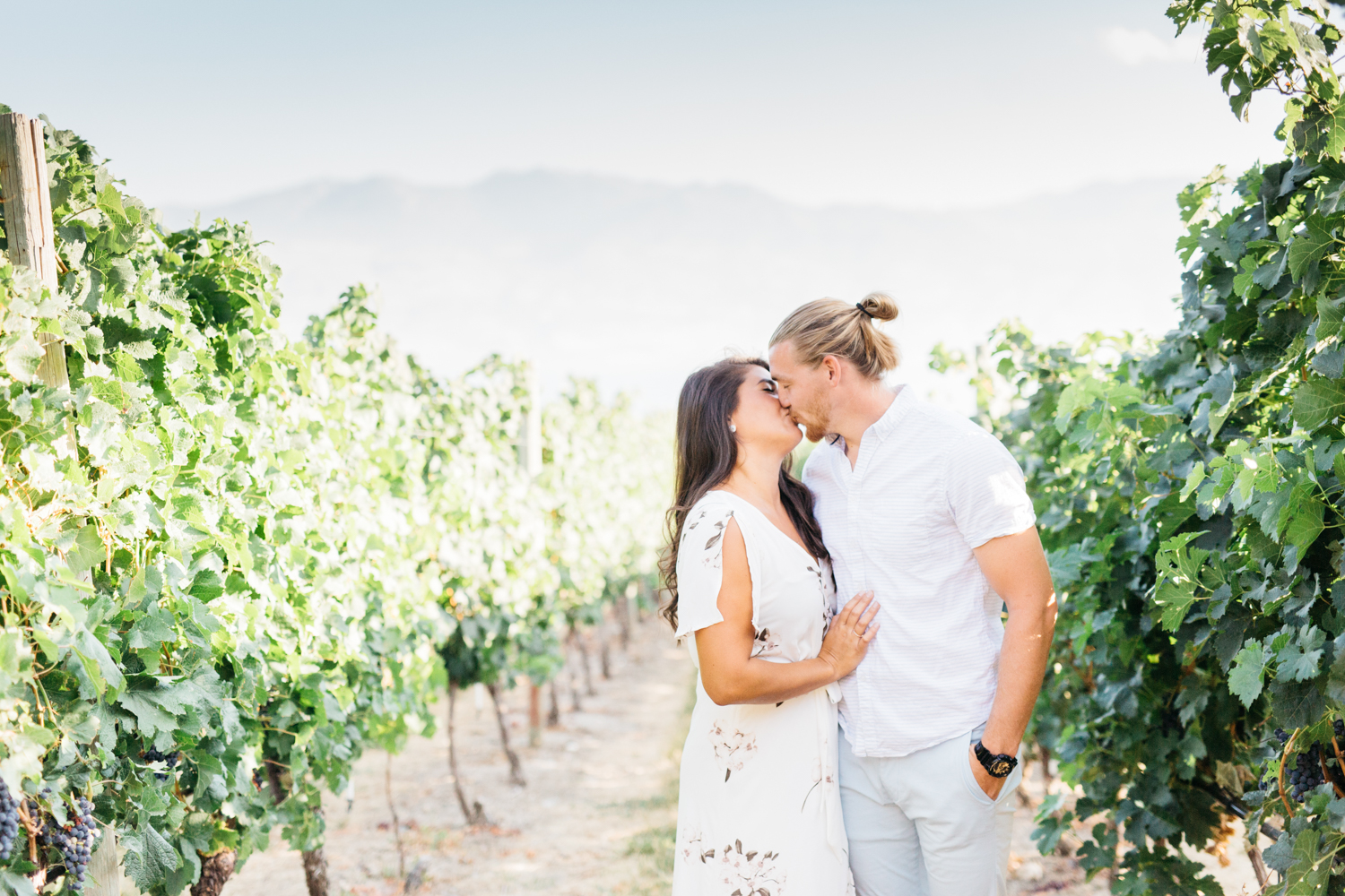 Couple kissing in vineyard at Quails' Gate Estate and Winery in Kelowna B.C