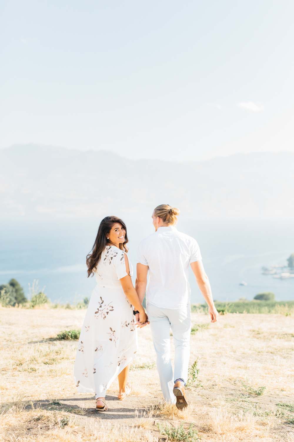 Couple walking with mountains in the background at Quails's Gate