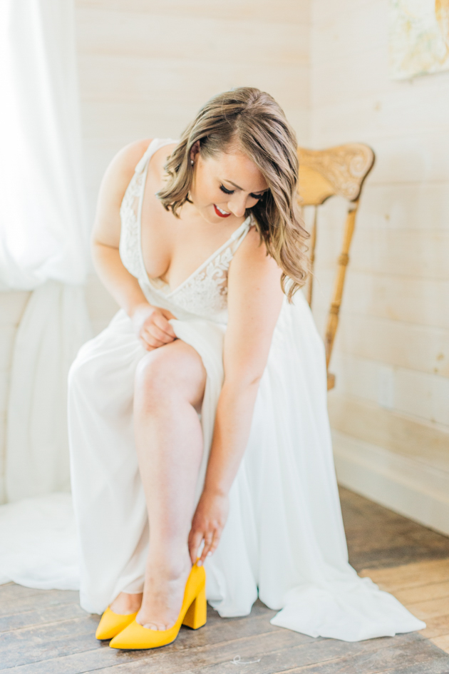 Bride putting on shoes at Stonewall Estates