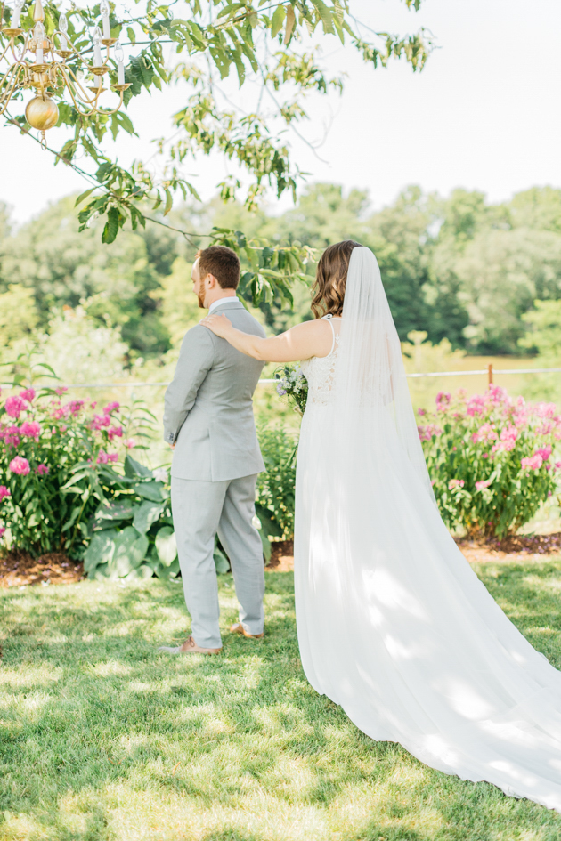 Bride tapping on groom's shoulder in first look