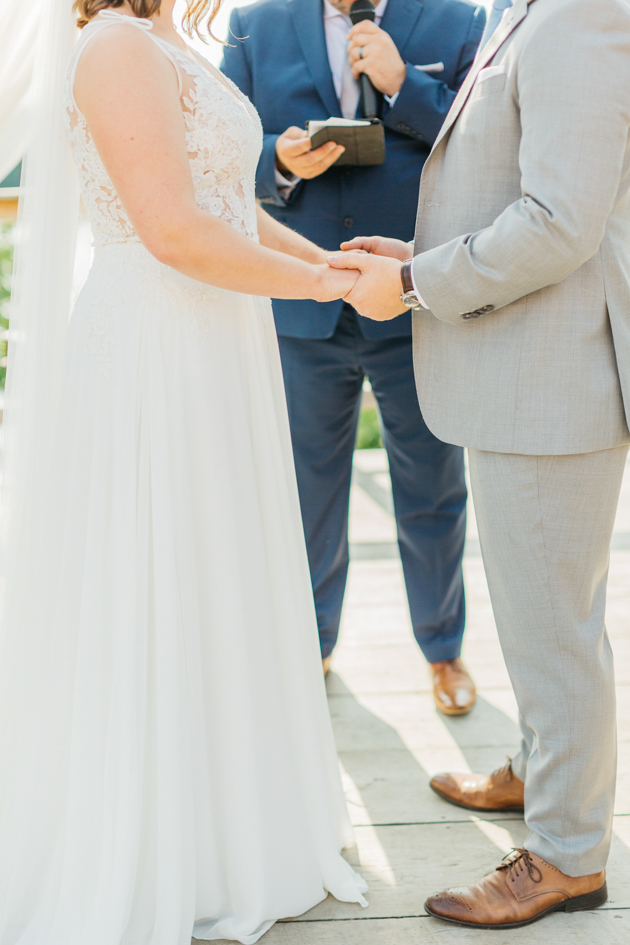 Bride and groom holding hands at ceremony